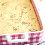 pinterest image of a pink casserole dish containing pudding made with rhubarb and eggs.