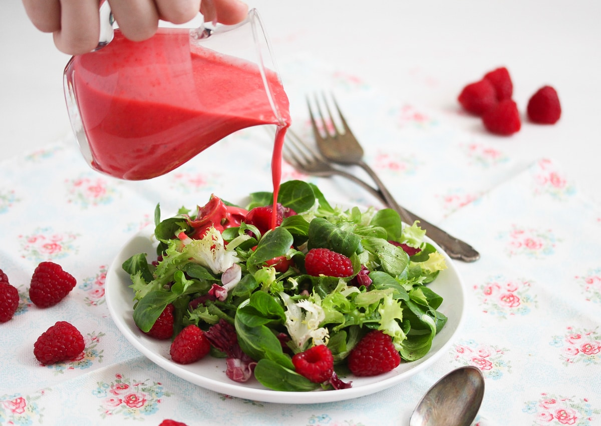 hand pouring raspberry dressing over salad