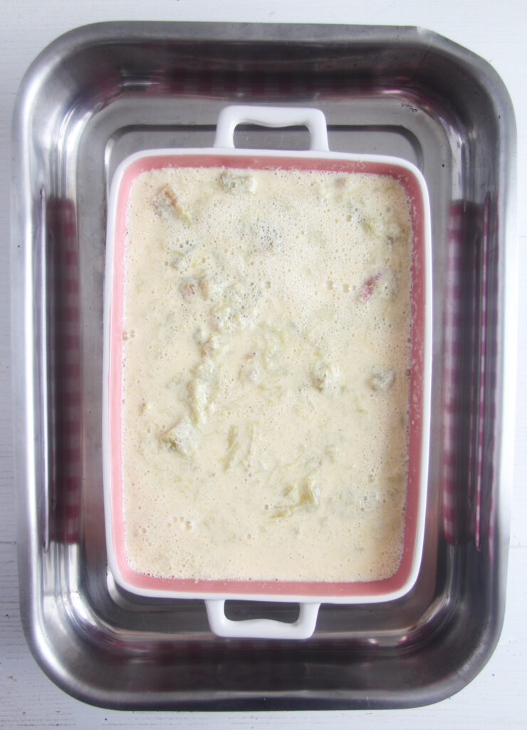 casserole dish containing rhubarb custard ready to baked in a larger baking dish filled with water.
