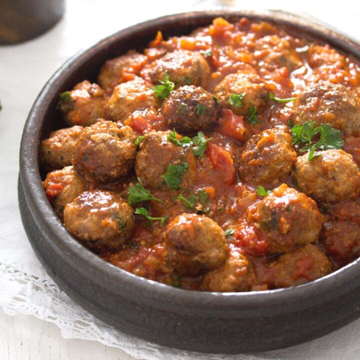 brown earthen bowl with spanish meatballs served as tapas in tomato sauce.
