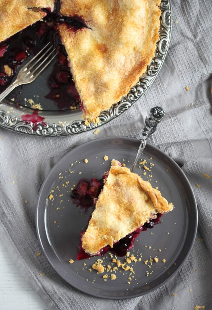 sliced blackberry rhubarb pie on a silver platter and a small plate