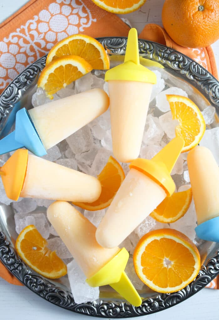 citrus pops on a silver platter with a oranges besides