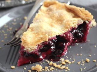 slice of rhubarb blueberry pie on a gray plate with a fork
