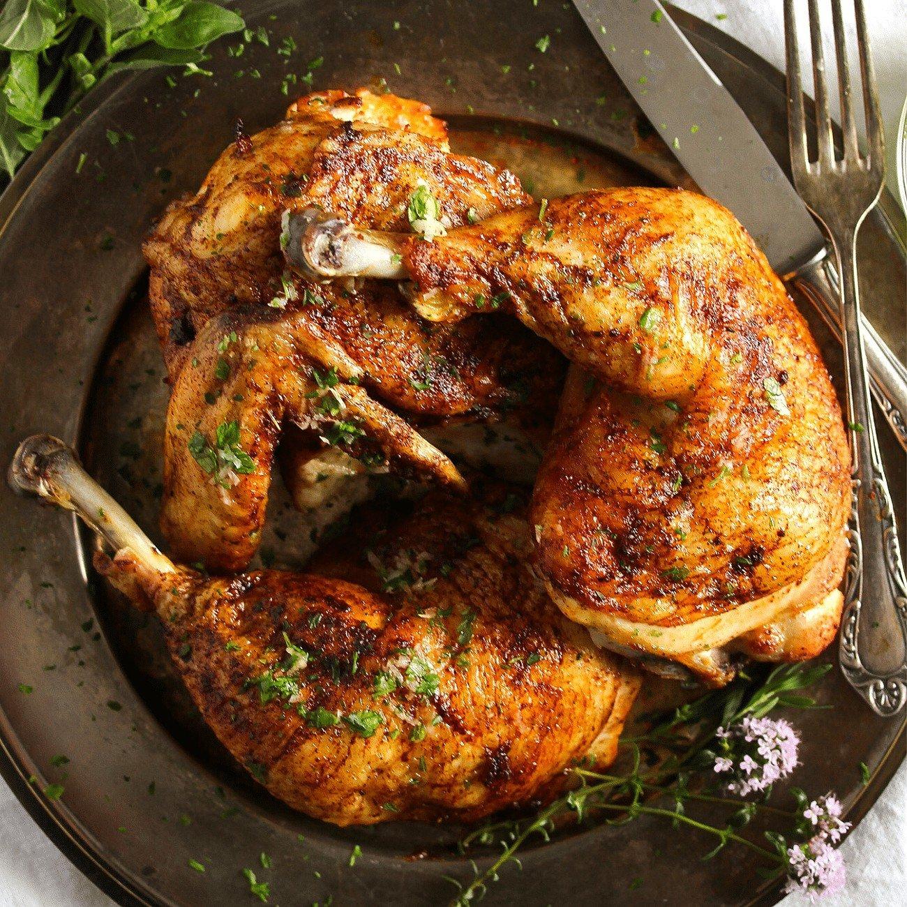 roasted half chicken on a dark plate