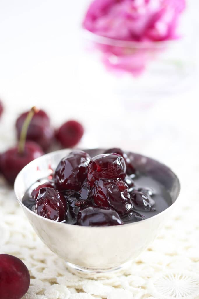 syrup and cherries in a small silver bowl with a rose behind