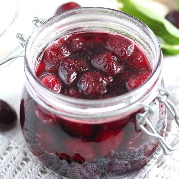 glossy amaretto cherries in a small jar