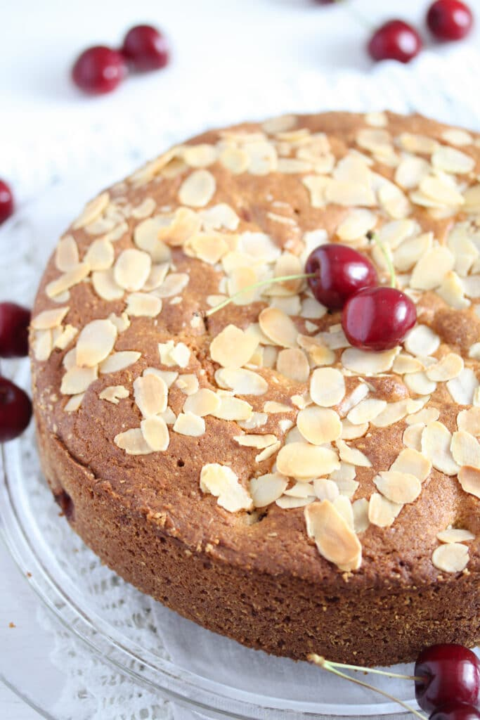 ground almond cake with fresh cherries on a platter