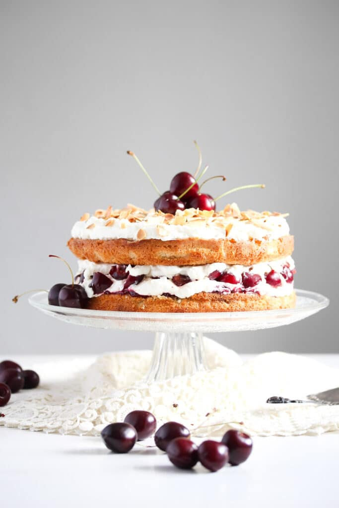 cherry bakewell cake on a tall cake platter with fresh cherries