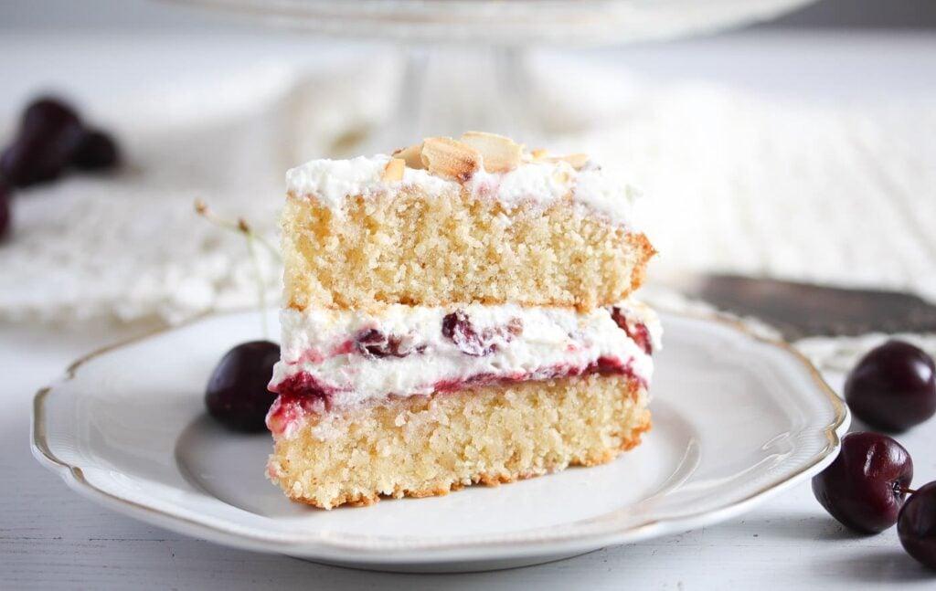 slice of cherry bakewell cake on a vintage platter