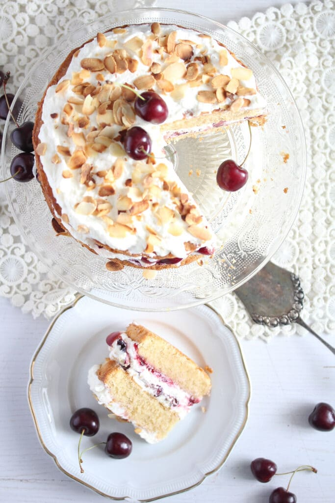 torte topped with toasted almonds and fresh cherries seen from above