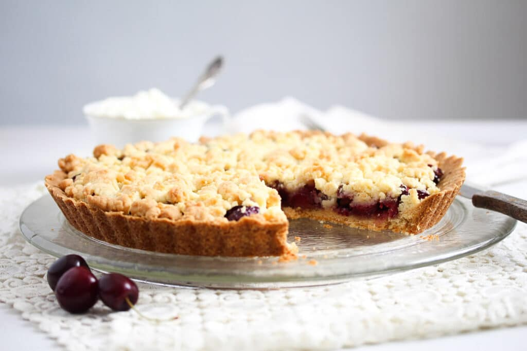 cherry crumble pie on a platter served with cream