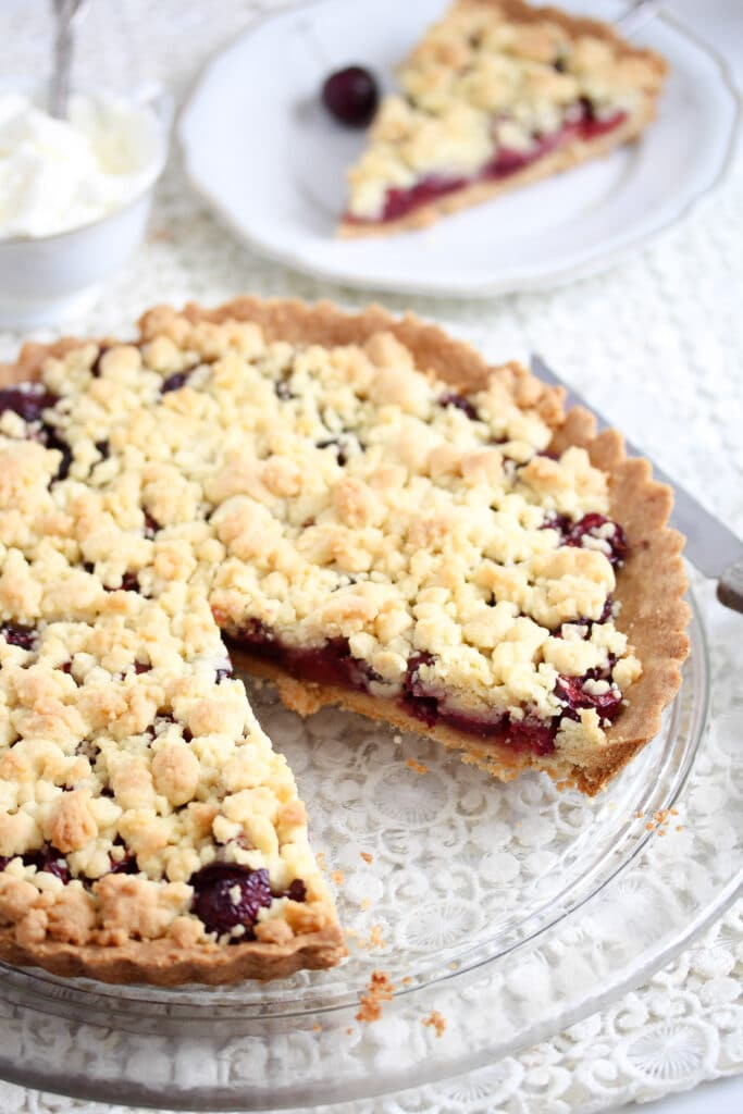 cherry crumb pie sliced on a platter