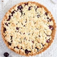 cherry crumb pie with golden topping on the table