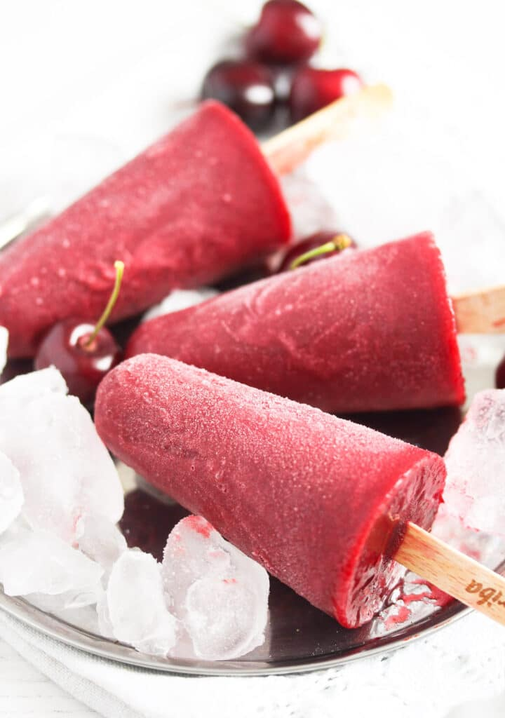 close up red ice pops with fresh cherries