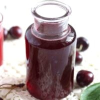 small bottle of cherry syrup on a white cloth.