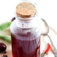 bottle of infused cherry vinegar with a cork lid