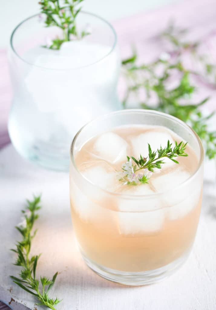 ginger and rhubarb gin in a small glass with thyme on top