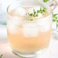 glass with flavored alcohol and a twig of thyme
