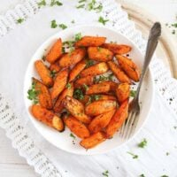 air fryer carrots sprinkled with parsley on a white plate with a fork