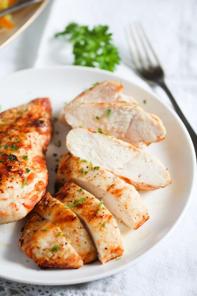 chicken breast slices on a white plate with parsley and a fork