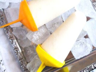 lime popsicles on a silver platter with ice cubes