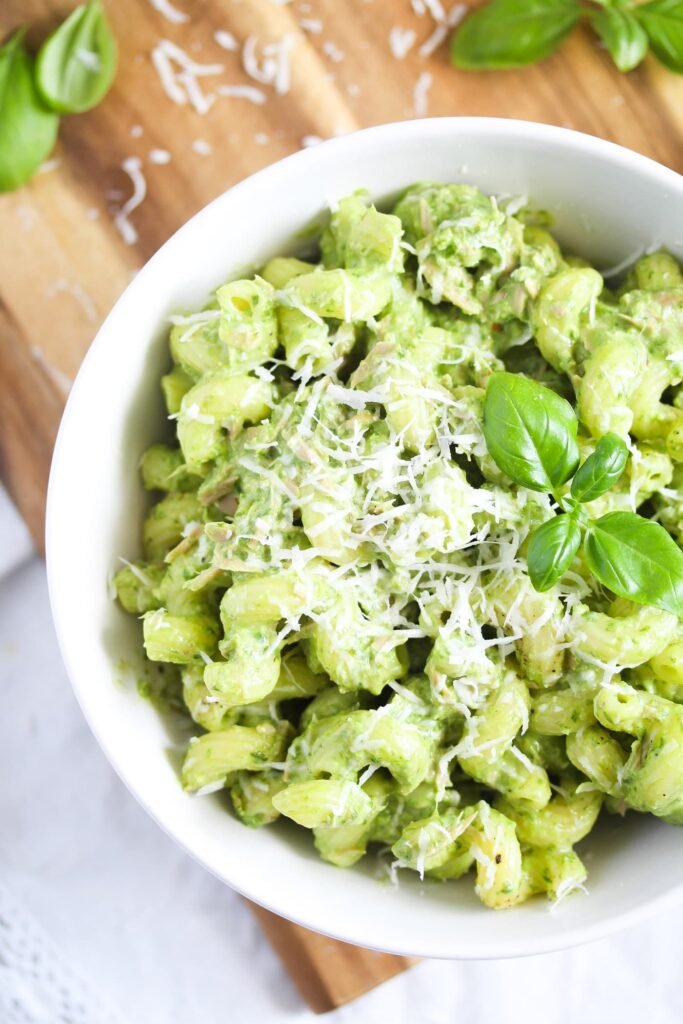 close up green tuna pasta sprinkled with parmesan and topped with basil leaves