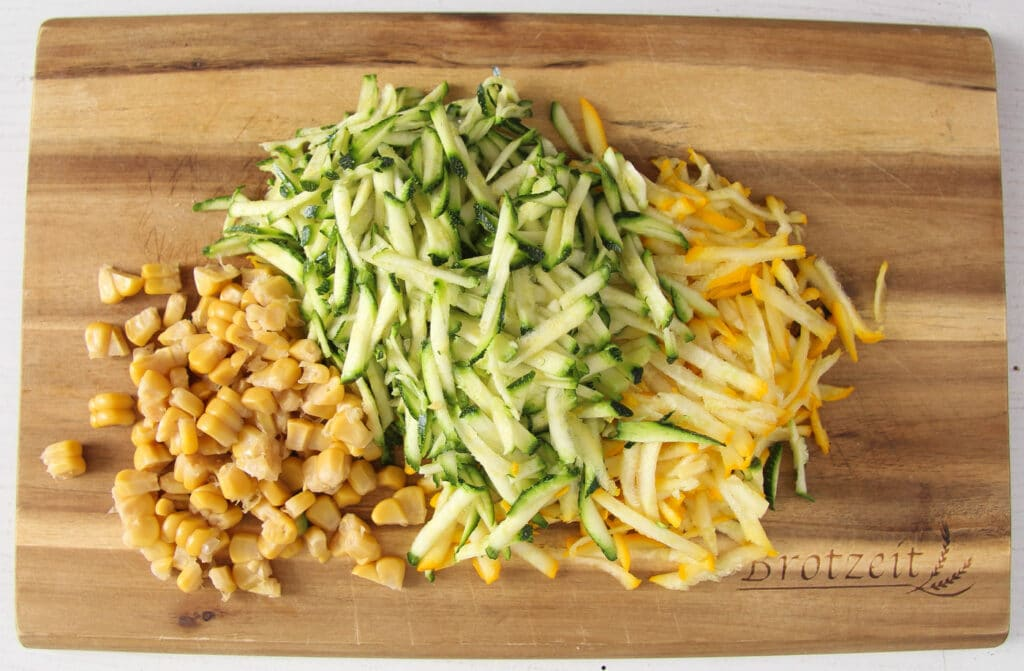 grated green and yellow zucchini and corn kernels on a wooden board