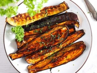air fryer eggplants with honey glaze on a white plate with parsley