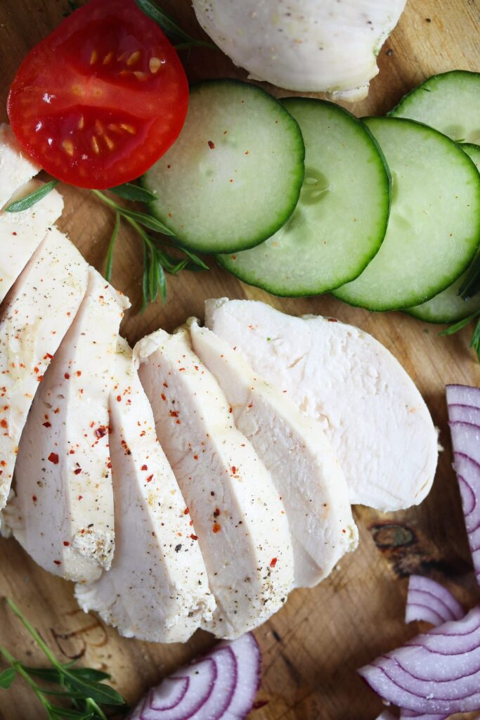 sliced boiled chicken breast on a wooden board with cucumbers