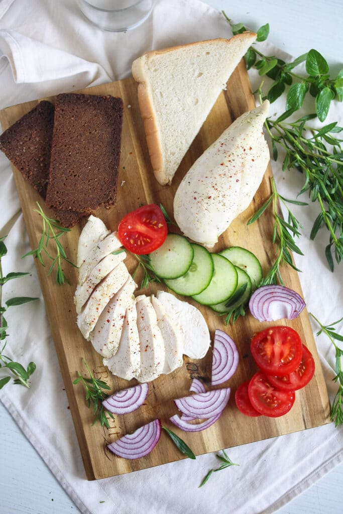 wooden board with poached chicken breast, dark bread and vegetables