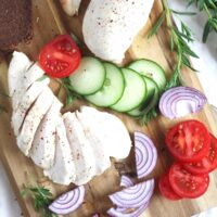 boiled frozen chicked breast sliced on a wooden board with tomatoes and red onions.