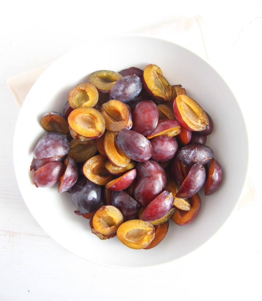 bowl with halved italian plums