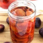 jar of canned plums with fruit around it