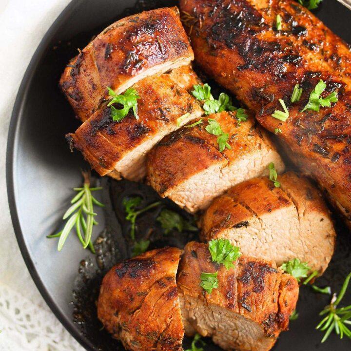 sliced cast iron pork tenderloin on a black plate