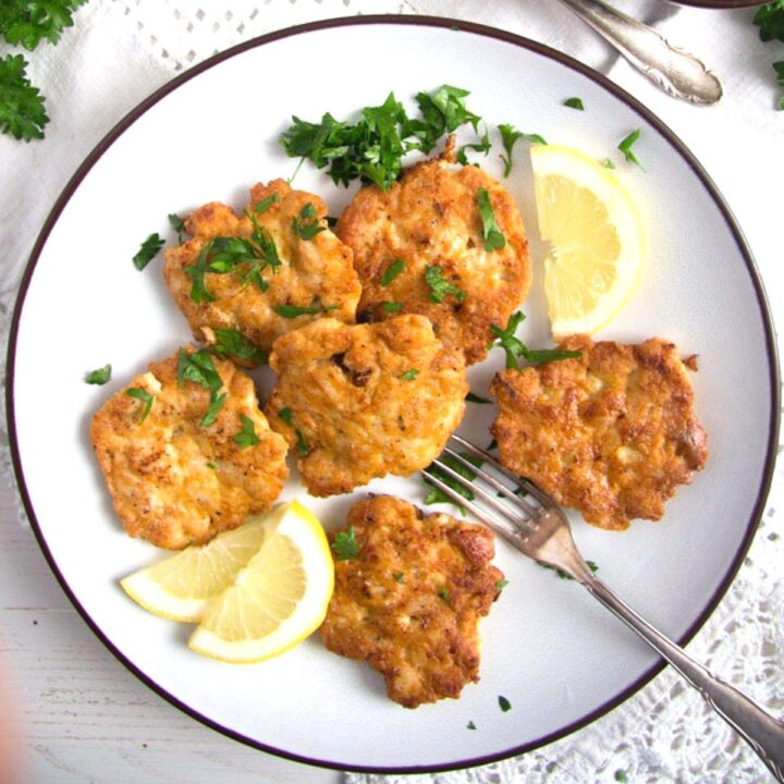 chicken breast patties on a plate with lemon slices.