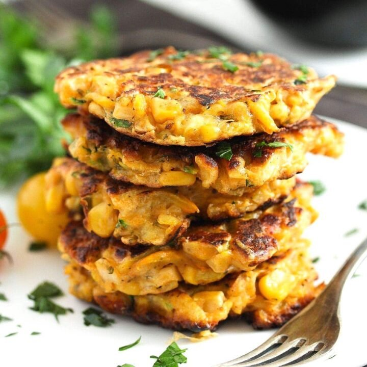 corn and zucchini fritters stapled on a white plate