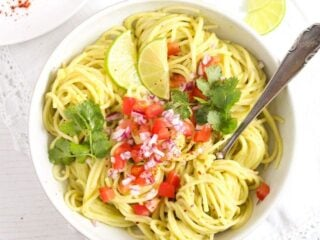 pasta guacamole in a white bowl sprinkled with tomatoes and onions