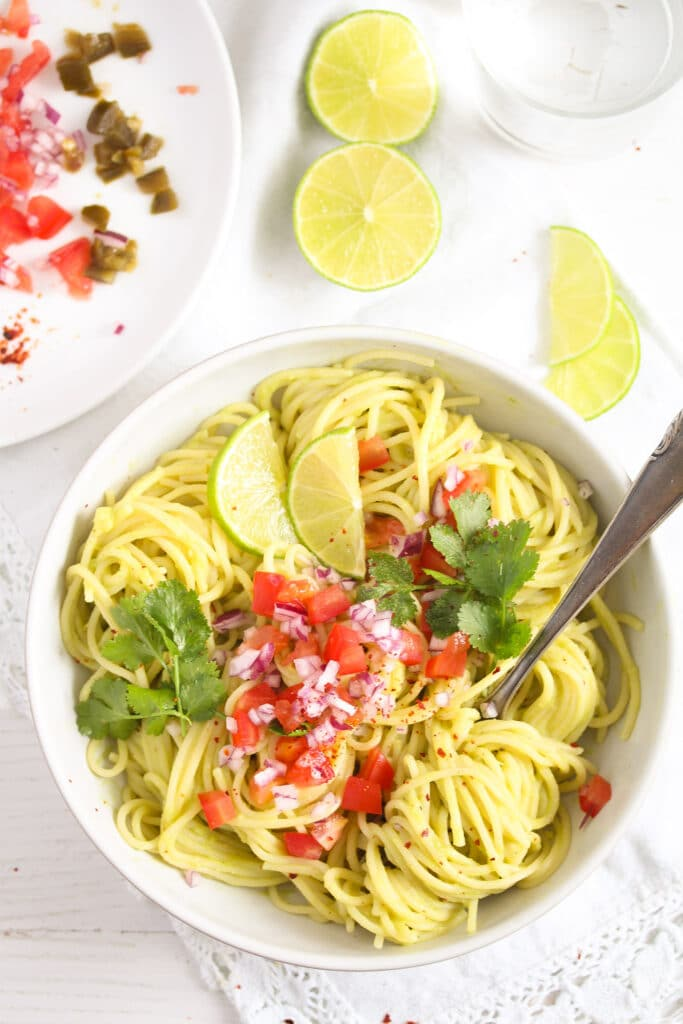 creamy guacamole pasta with lime wedges seen from above