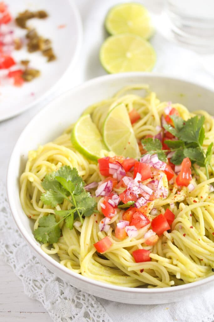 guacamole spaghetti with chopped tomatoes and cilantro in a white bowl
