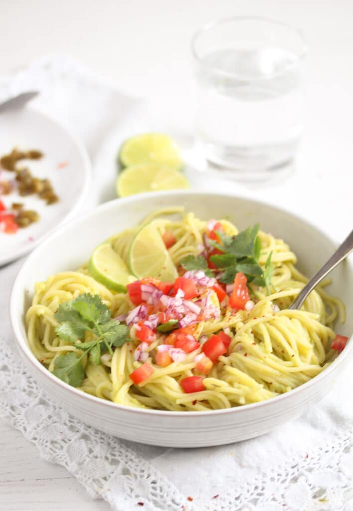 avocado pasta with chopped tomatoes and onions in a bowl