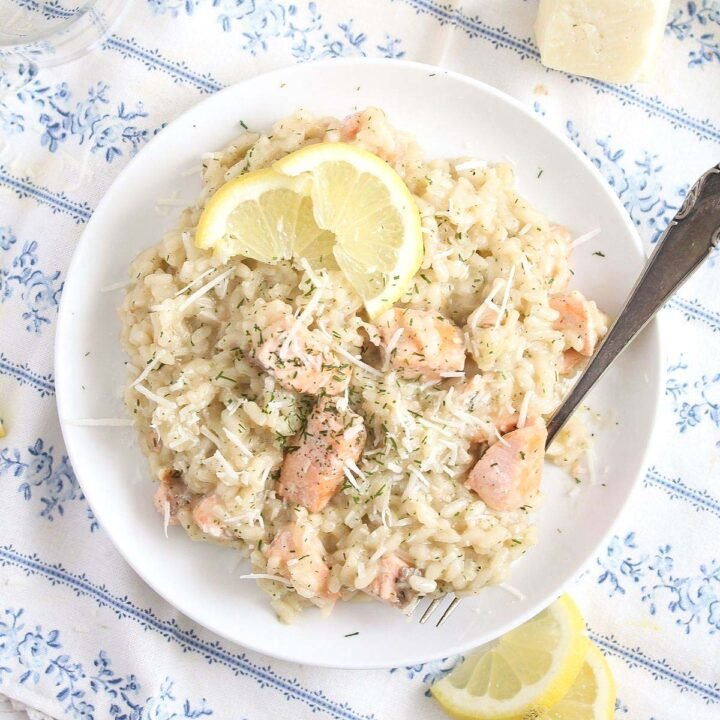 salmon risotto with dill and parmesan on a white plate