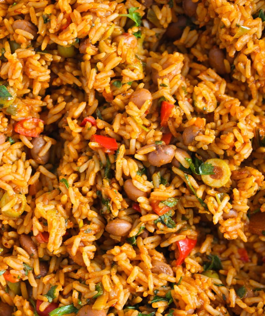 close up orange colored rice with vegetable pieces inside