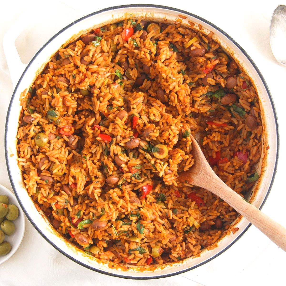 spanish rice and beans with olives and peppers in a white pot