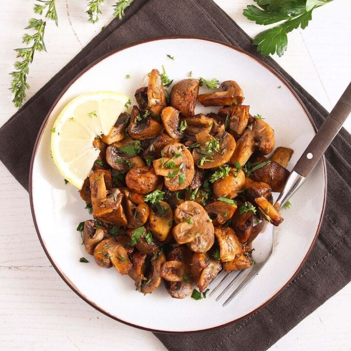 air fryer mushrooms served with lemon wedgeds on a white plate
