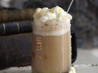 boozy butterbeer topped with whipped cream and butterscotch syrup in a mug