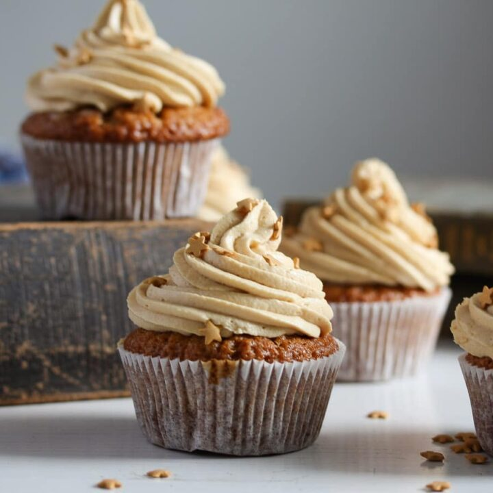 butterscotch muffins frosted with cream arranged on old books