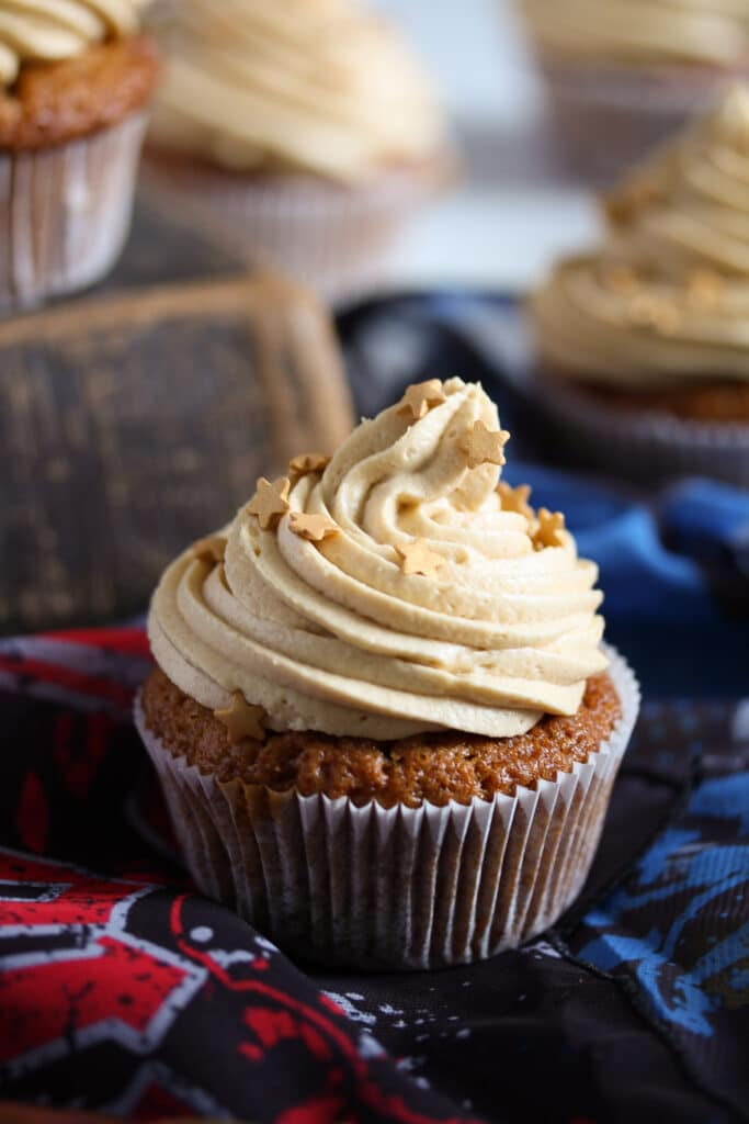 cupcake with butterscotch frosting on blue and red scarves