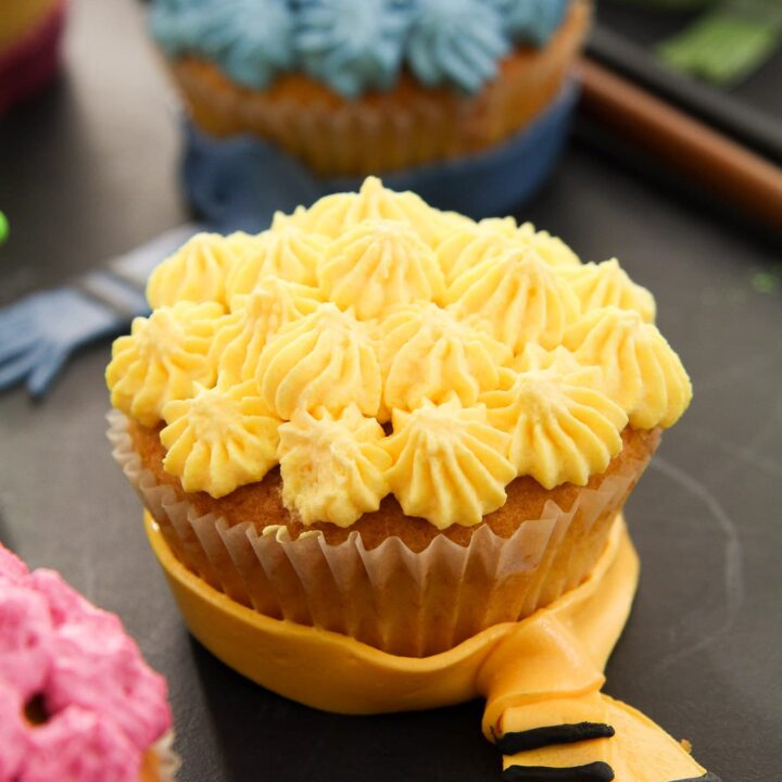 yellow hufflepuff cupcake decorated with whipped cream and a fondant scarf