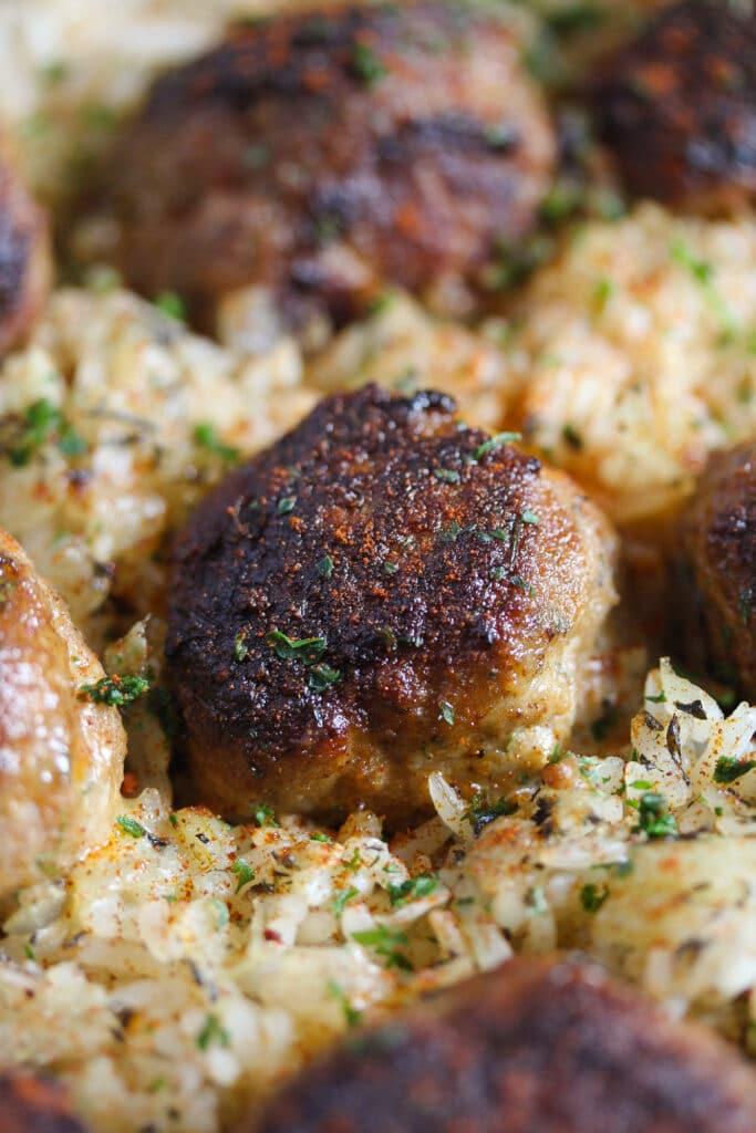 close up of one brown meatball on rice