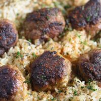 brown meatballs with rice and sprinkled with parsley